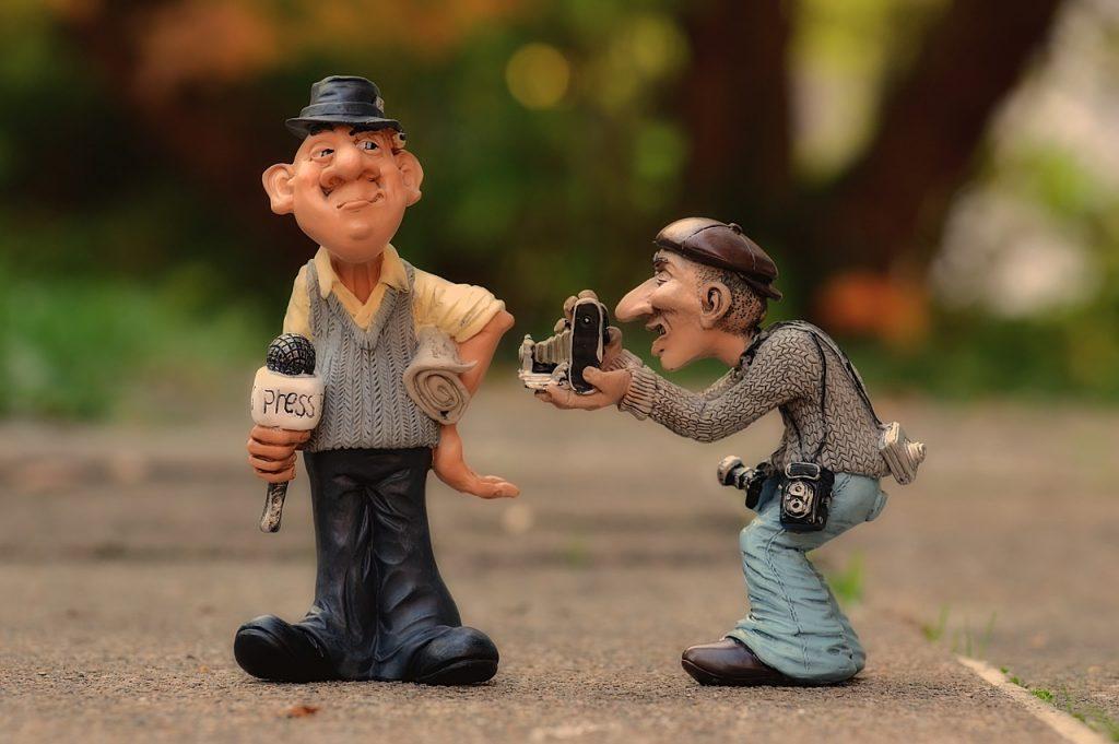 Periodista y fotógrafo representados con figuras